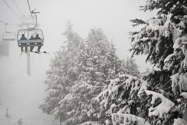 A skier and snowboarders ride the Ted's Express chairlift at Alyeska Resort into the fog on March 14, 2018, in Girdwood. (Marc Lester / ADN)