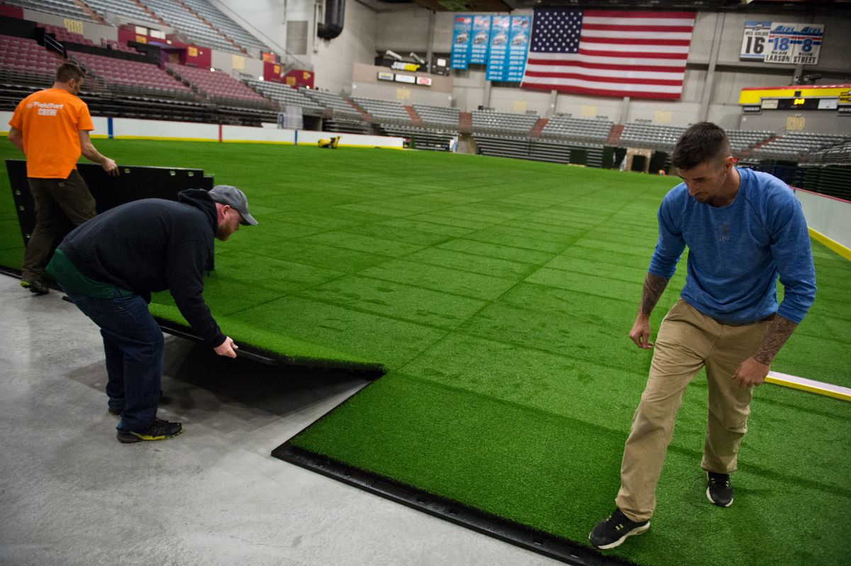 Kenyon DePriest of Palmer, left, Jack Nolan of Boston and Brian Garland of Maine install artificial turf Monday at Sullivan Arena. The arena's general manager said the playing field will be available for use by the end of the month. (Marc Lester / ADN)