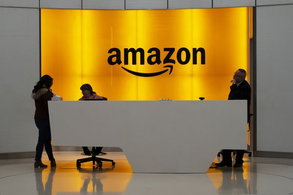 """FILE - In this Feb. 14, 2019, file photo people stand in the lobby for Amazon offices in New York. Amazon says President Donald Trump's """"improper pressure"""