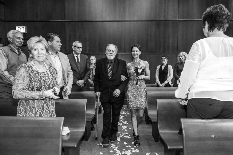 Rich Volk walks his daughter Ashley down an aisle sprinkled with rose petals, compliments of the judge, in Chicago, Oct. 31, 2017. (Devin Yalkin/The New York Times)