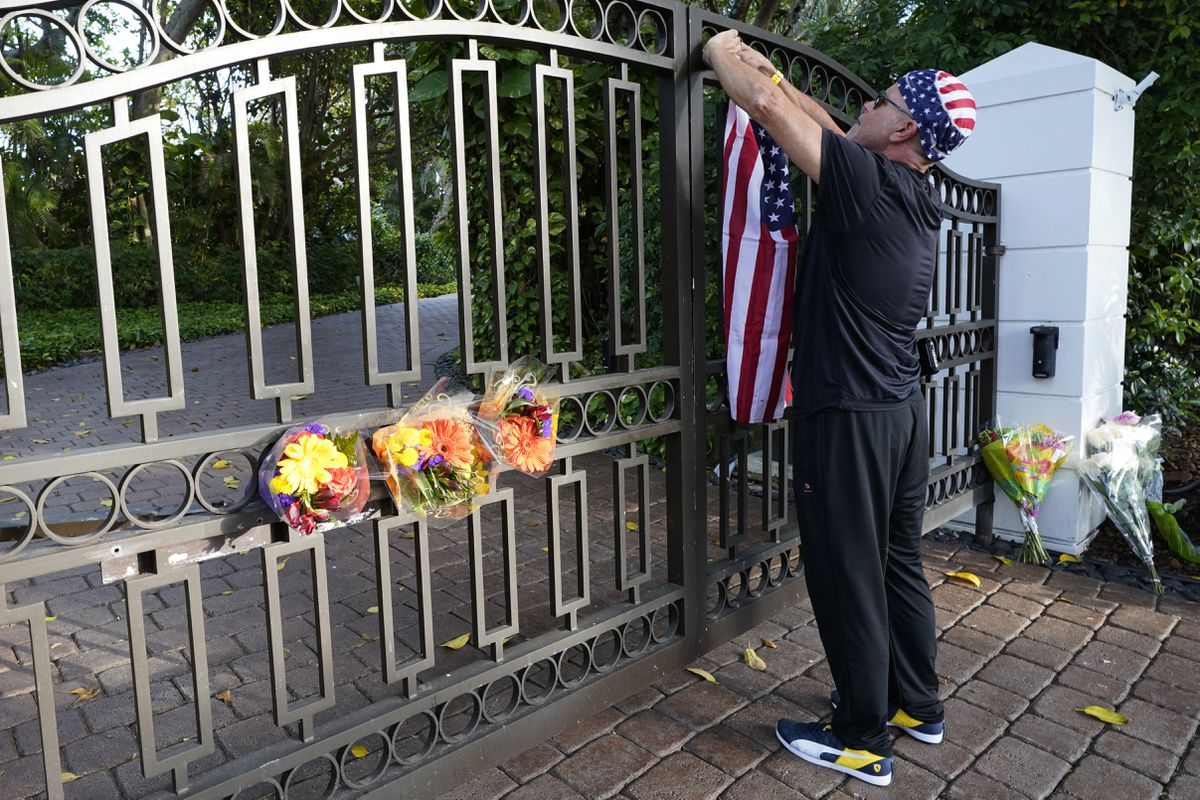 John Hensel attaches an American flag to the gate of the home of his friend and talk radio host Rush Limbaugh, Wednesday, Feb. 17, 2021, in Palm Beach, Fla. Limbaugh, 70, died this morning of lung cancer. (AP Photo/Marta Lavandier)