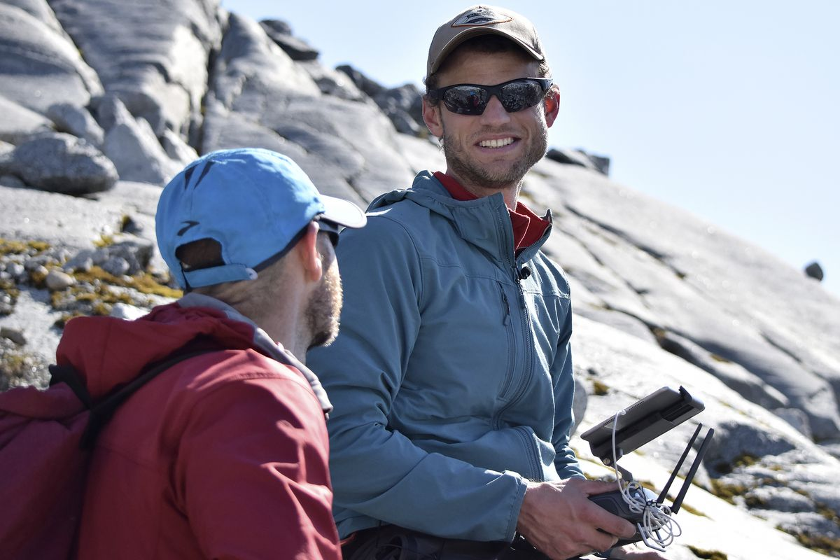 This June 21, 2019, photo shows University of Alaska Southeast environmental science professor Christian Kienholz, right, speaking with Gabriel Wolken, research assistant professor at the University of Alaska Fairbanks, while surveying Suicide Basin using a drone near Juneau, Alaska. A number of local scientists are studying changes to Suicide Basin, but Kienholz is one of the only ones using drones to analyze ice and water levels in the basin. (Nolin Ainsworth/The Juneau Empire via AP)