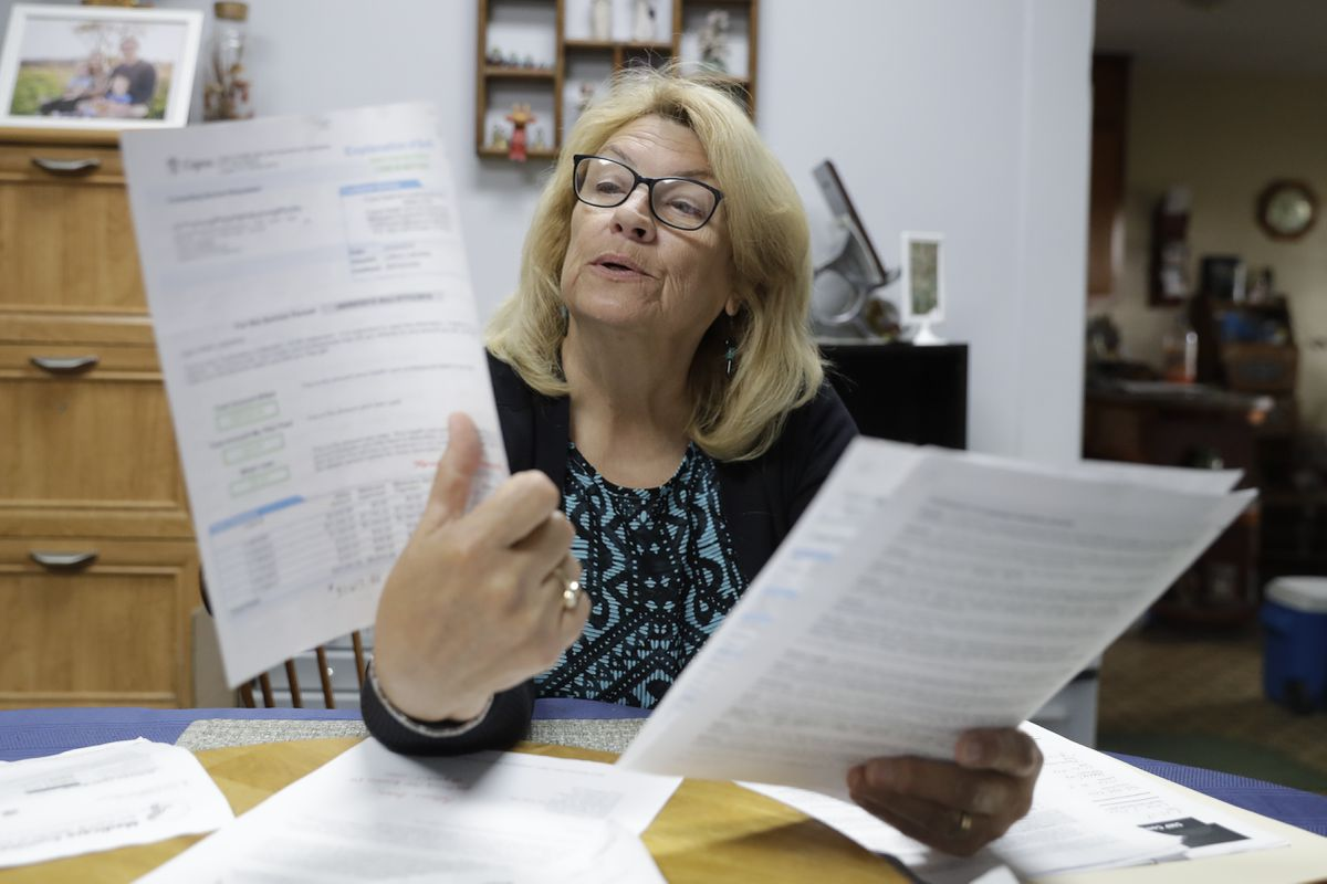 Linda Morris looks over her Medicare statements, Wednesday, Sept. 25, 2019, in Parker City, Ind. Federal law enforcement officials say they've taken down a nearly-$2 billion Medicare fraud scheme that exploited curiosity about genetic medicine by having seniors get their cheeks swabbed for unneeded DNA tests. A Medicare enrollee, Morris said she was roped in at a conference on aging well. The retired high school math and journalism teacher got her cheek swabbed by one of the many health vendors at the event. (AP Photo/Darron Cummings)