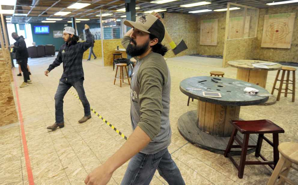 Raymond Mata, center, and Isaac Cortez, owners and co-founders of Alaska Axe Co., throw axes at their recently opened business near the corner of East 68th Avenue and Lake Otis Parkway on Sept. 22. (Bill Roth / ADN)