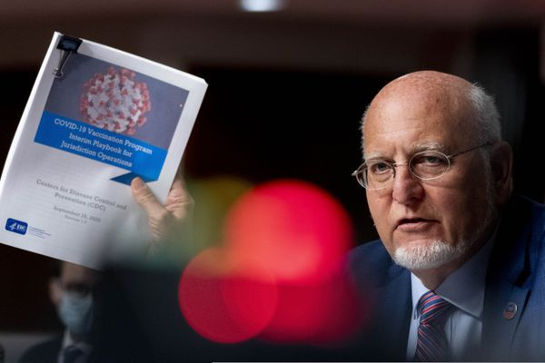 Centers for Disease Control and Prevention Director Dr. Robert Redfield holds up a CDC document that reads