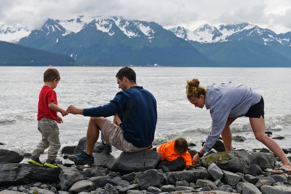 Ryan Shaver, right, talks with his 3-year-old son, Liam, by the water in Seward at left. Jessica Shaver reaches for 1-year-old Rinette, on June 23, 2018. (Marc Lester / ADN)
