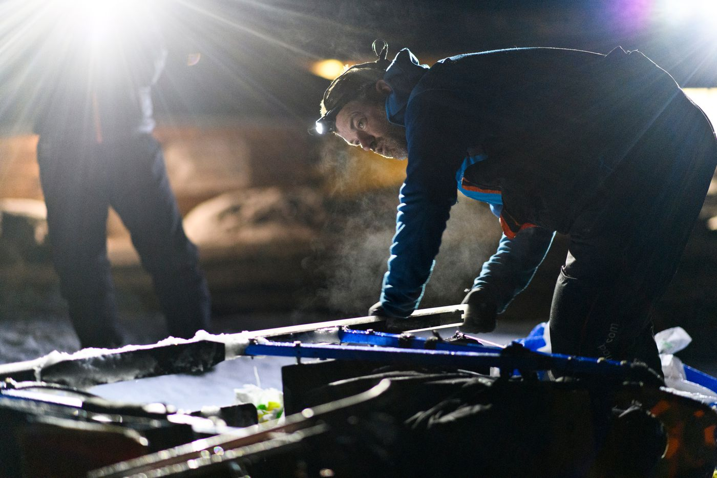 Jason Campeau works on his sled runners while stopped in Shageluk during the 2019 Iditarod Trail Sled Dog Race on March 8, 2019. (Marc Lester / ADN)