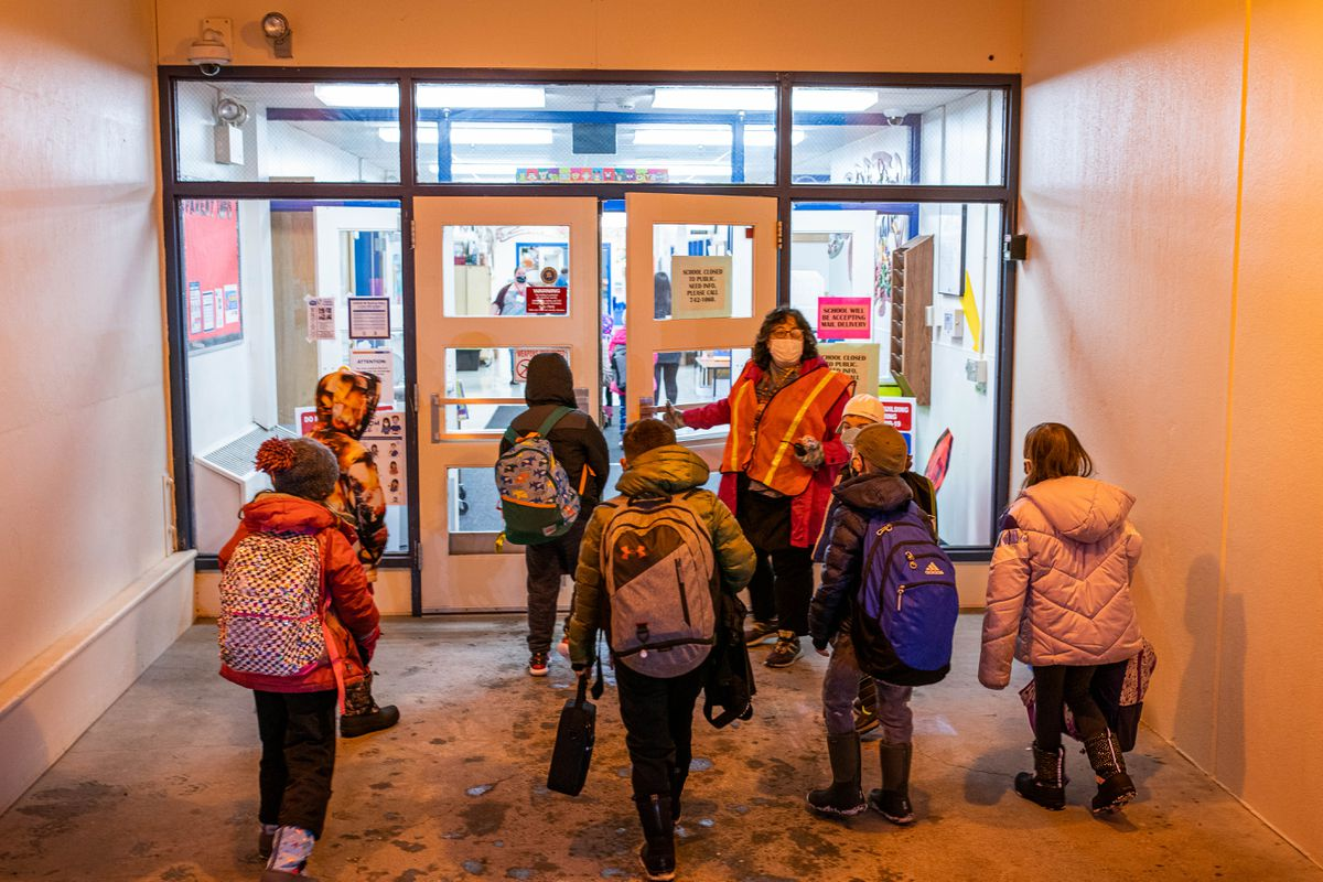 Tudor Elementary principal Nicole Sommerville lets students into the building on the first day of in-person learning Wednesday, Jan. 20, 2021 at Tudor Elementary School. (Loren Holmes / ADN)