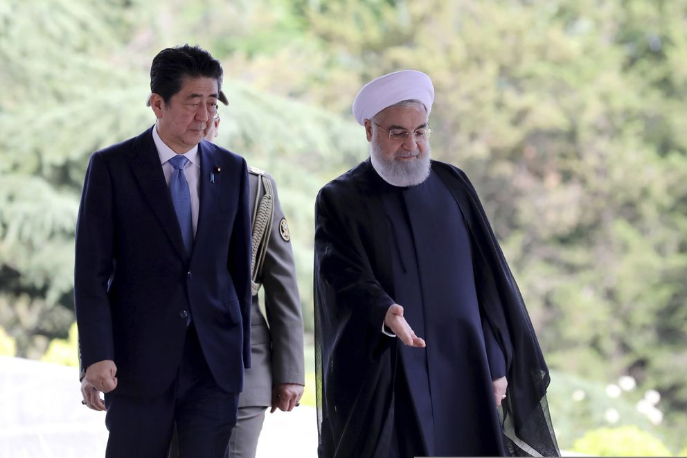 Japanese Prime Minister Shinzo Abe, left, is welcomed by Iranian President Hassan Rouhani, during an official arrival ceremony at the Saadabad Palace in Tehran, Iran, Wednesday, June 12, 2019. The Japanese leader is in Tehran on an mission to calm tensions between the U.S. and Iran. (AP Photo/Ebrahim Noroozi)