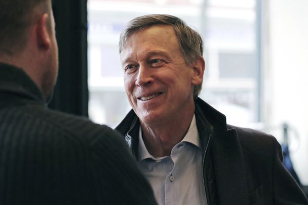 FILE - In this March 22, 2019, file photo, former Democratic Colorado Gov. John Hickenlooper talks with AmeriCorps members prior to a roundtable campaign stop in Manchester, N.H. Hickenlooper is proposing a $15 federal minimum wage _ with a twist. Rather than unilaterally hiking the national wage to $15, the former Colorado governor proposes phasing in the increases based on the cost of living. (AP Photo/Charles Krupa, File)