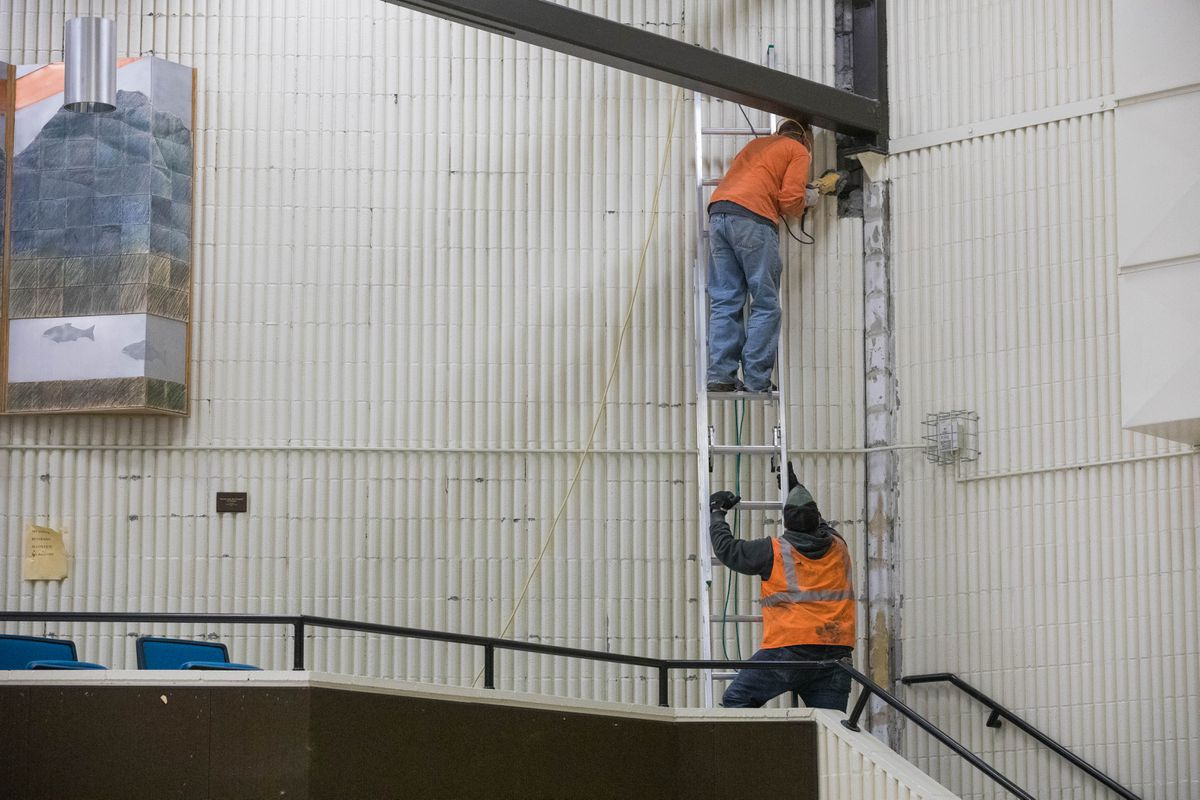 Workers remove damaged concrete siding inside Gruening Middle School in Eagle River on Tuesday, Dec. 4, 2018, after the 7.0 earthquake. Funding for earthquake-related repairs at the school is included in the Anchorage School District's 2020 bond proposal. (Loren Holmes / ADN)