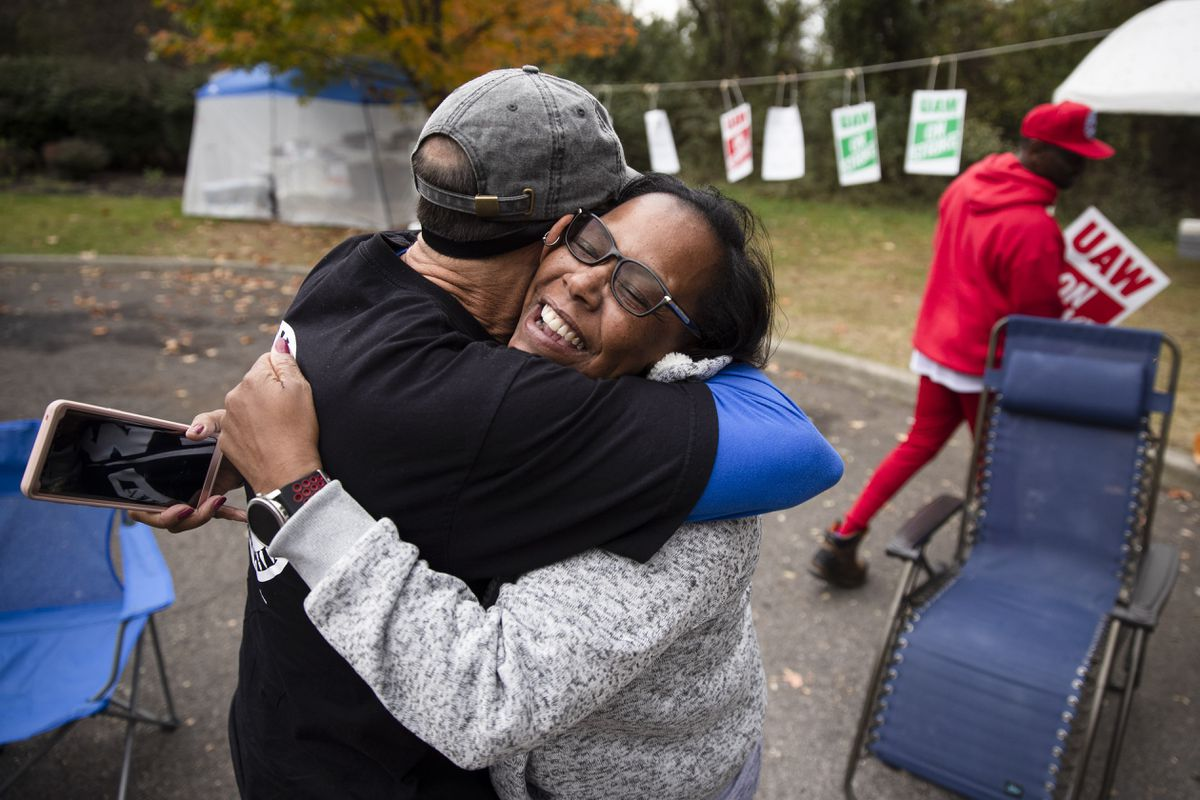 Picketing United Auto Workers Richard Rivera, left, and Robin Pinkney react to news of a tentative contract agreement with General Motors, in Langhorne, Pa., Wednesday, Oct. 16, 2019. (AP Photo/Matt Rourke)