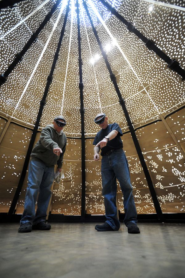 """Brothers Bill Carr, from Estero, FL, and Bruce Carr, from Anchorage, use virtual reality glasses to tour the """"Murmur: Arctic Realities"""" installation at the Anchorage Museum in Anchorage, AK on Friday, Aug 10, 2018. (Bob Hallinen / ADN)"""