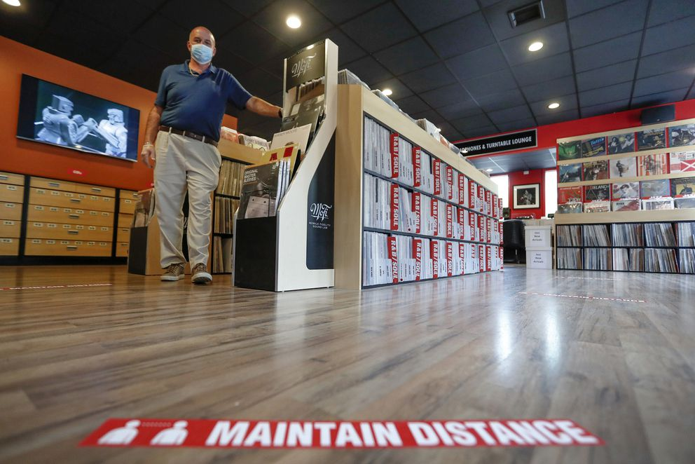 Mark Mawhinney walks past one of the racks of records towards the sticker on the floor reminding customers to maintain distances in his 'Music to My Ears ' retail record and HiFi store, Thursday, May 14, 2020, in Pittsburgh. He was preparing the store to re-open Friday when some of the COVID-19 restrictions will be lessened in Pittsburgh and several western Pennsylvania counties as they move from red to yellow status. (AP Photo/Keith Srakocic)