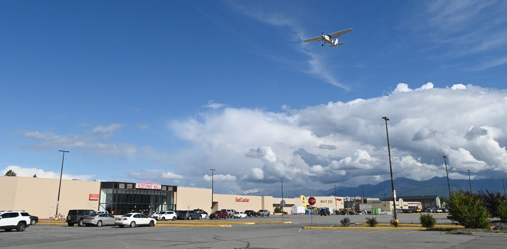 A small airplane passes over the Northway Mall parking lot while landing at Merrill Field Airport on Thursday, August 27, 2020. The Northway Mall plans to close common spaces on Sept. 30 (Bill Roth / ADN)