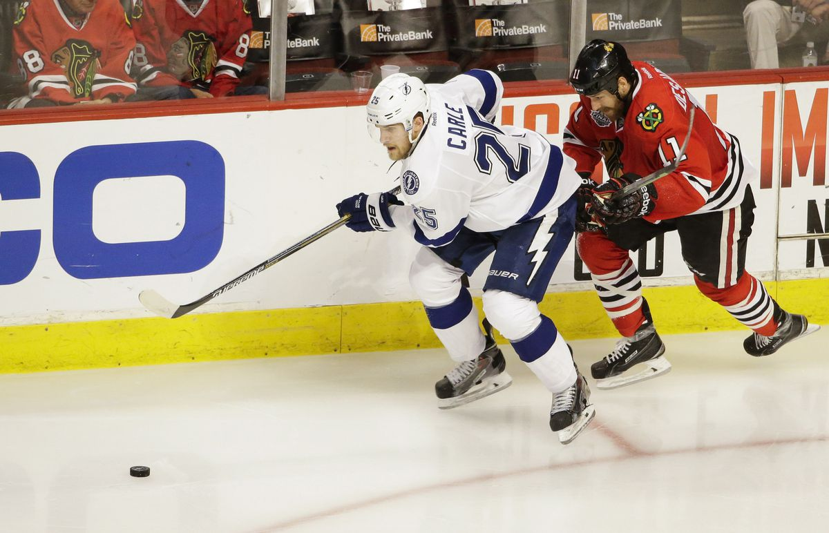 Tampa Bay Lightning defenseman Matt Carle (25) keeps the puck away from Chicago Blackhawks center Andrew Desjardins (11) during Game 6 of the 2015 Stanley Cup Final in Chicago. (Dirk Shadd/Tampa Bay Times/TNS)