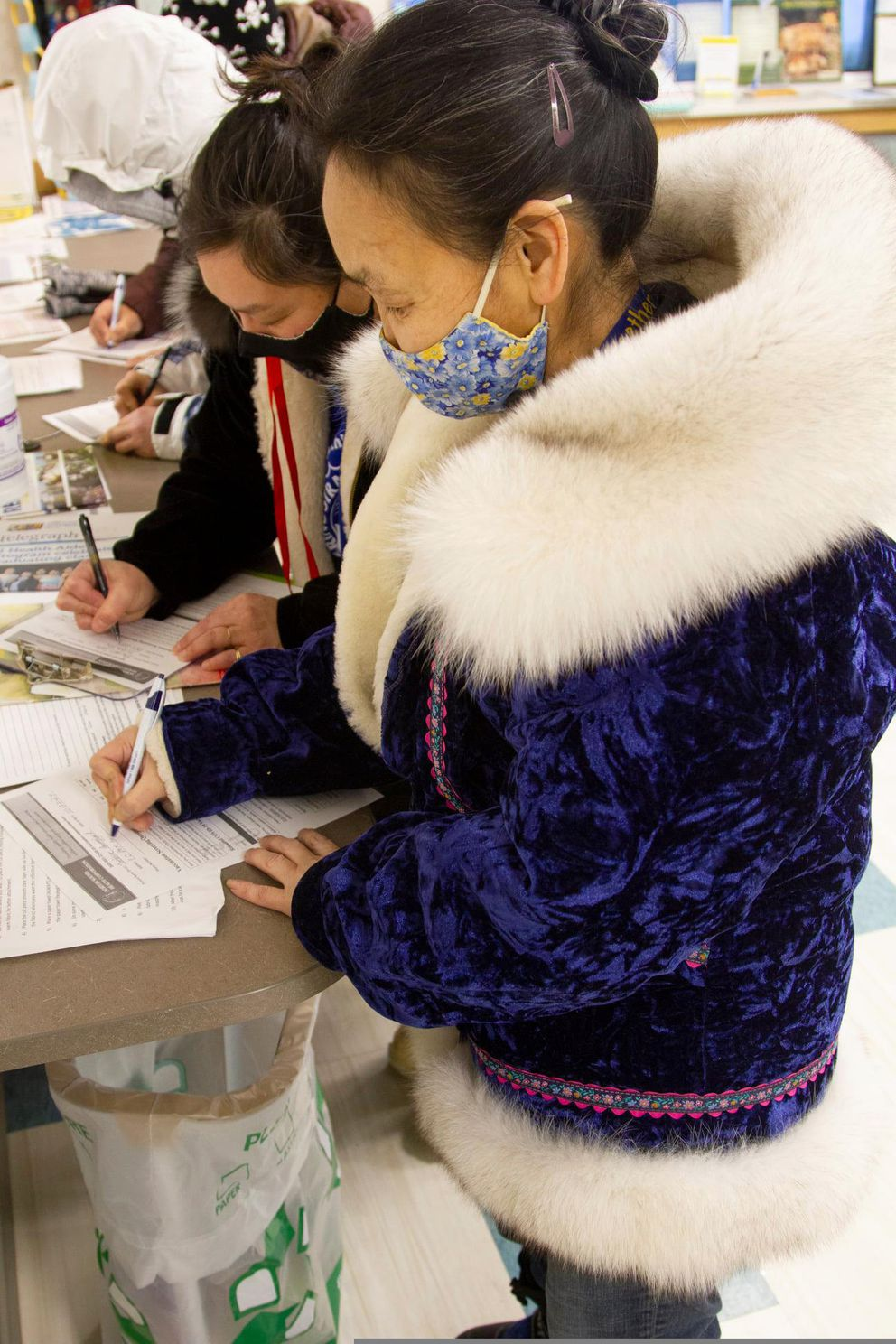 In this photo, provided by Norton Sound Health Corp., are Joey Annogiyuk, left, and Miriam Toolie signing up to receive the Pfizer vaccine at the Savoonga Clinic in Savoonga, Alaska, on Jan. 14, 2021. Some of Alaska's highest vaccination rates among those 16 or older have been in some of its remotest, hardest-to-access communities, where the toll of past flu or tuberculosis outbreaks hasn't been forgotten. (Reba Lean/Norton Sound Health Corp. via AP)