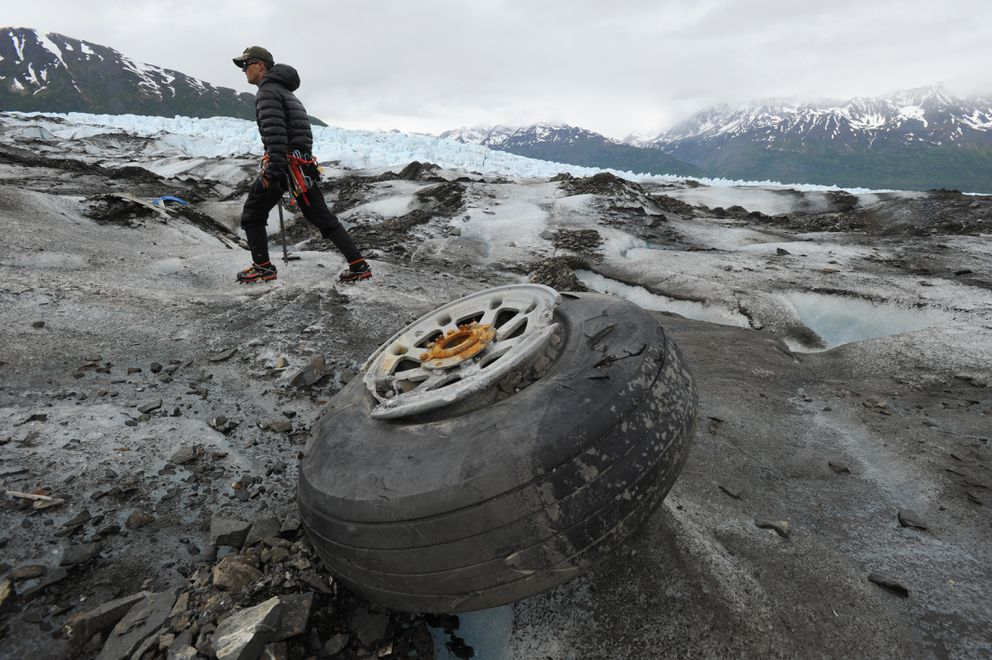 U.S. Marines Capt. David Gooch, with the Defense POW/MIA Accounting Agency, walks past an aircraft wheel assembly resting on the ice surface of Colony Glacier in Alaska on Wednesday, June 10, 2015. A team of military members and scientists are combing the surface of Colony Glacier looking for remains and personal effects that can be used to identify the 52 people who perished when a U.S. Air Force Douglas C-124 Globemaster II crashed into Mount Gannett, about 15 miles away, while flying in severe weather in 1952.