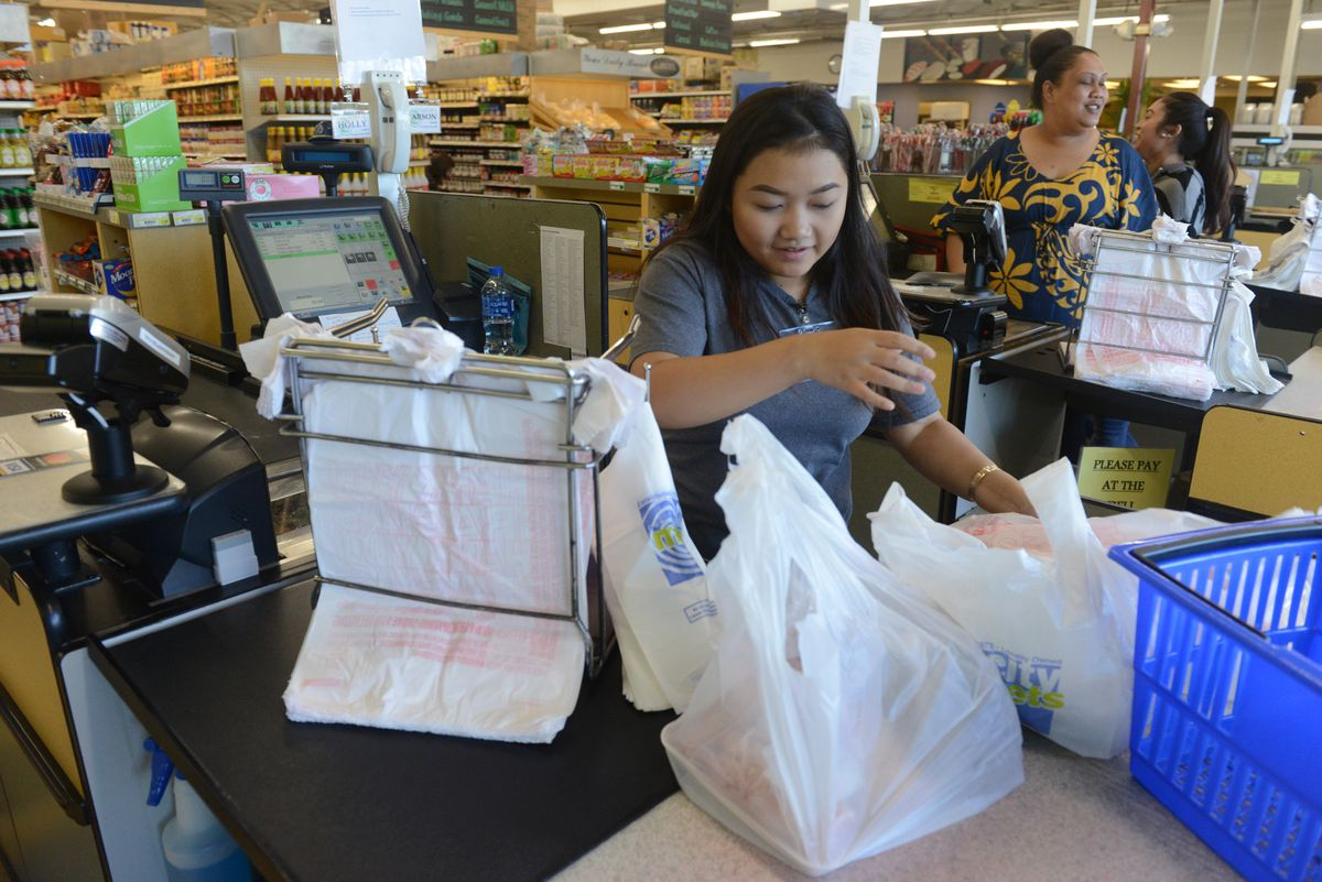 Rose Khotesouvan, a cashier at New Sagaya Midtown Market, bags customers groceries in Anchorage, AK on Wednesday, August 29, 2018. Assistant manager Rochelle Sortonis said they have seen an increase in customers bringing in reusable bags since talk of a plastic bag ban started. (Bob Hallinen / ADN)
