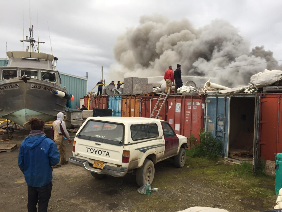 People watch a fire near the Dillingham harbor on Friday, July 27, 2018. (Avery Lill / KDLG)