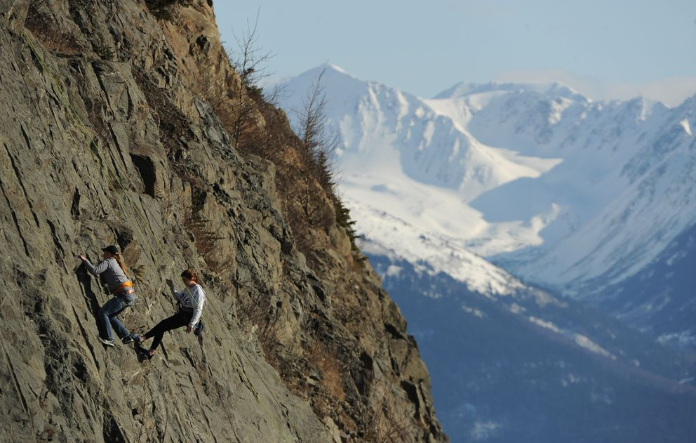 Olivia Pittman climbs up one of the Shot Rock routes as MiKylie Stephen rappels down along Seward Highway above Turnagain Arm on Friday, March 30, 2018. (Bob Hallinen / ADN)