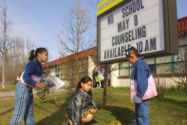 Mountain View Elementary School students Aneishe Thomas, left, Azure Sue, center, and Nikita Sanders look at a bouquet of flowers placed in front of their Anchorage, Alaska school, Tuesday, May 8, 2001, left for the four Mountain View students who were stabbed Monday. Parents came to the school Tuesday concerned about what they say is lax security at the elementary school where a man slashed four children with a filet knife. Court records indicate suspect Jason Pritchard had talked for years about killing children before Monday's attack. (AP Photo/Al Grillo)