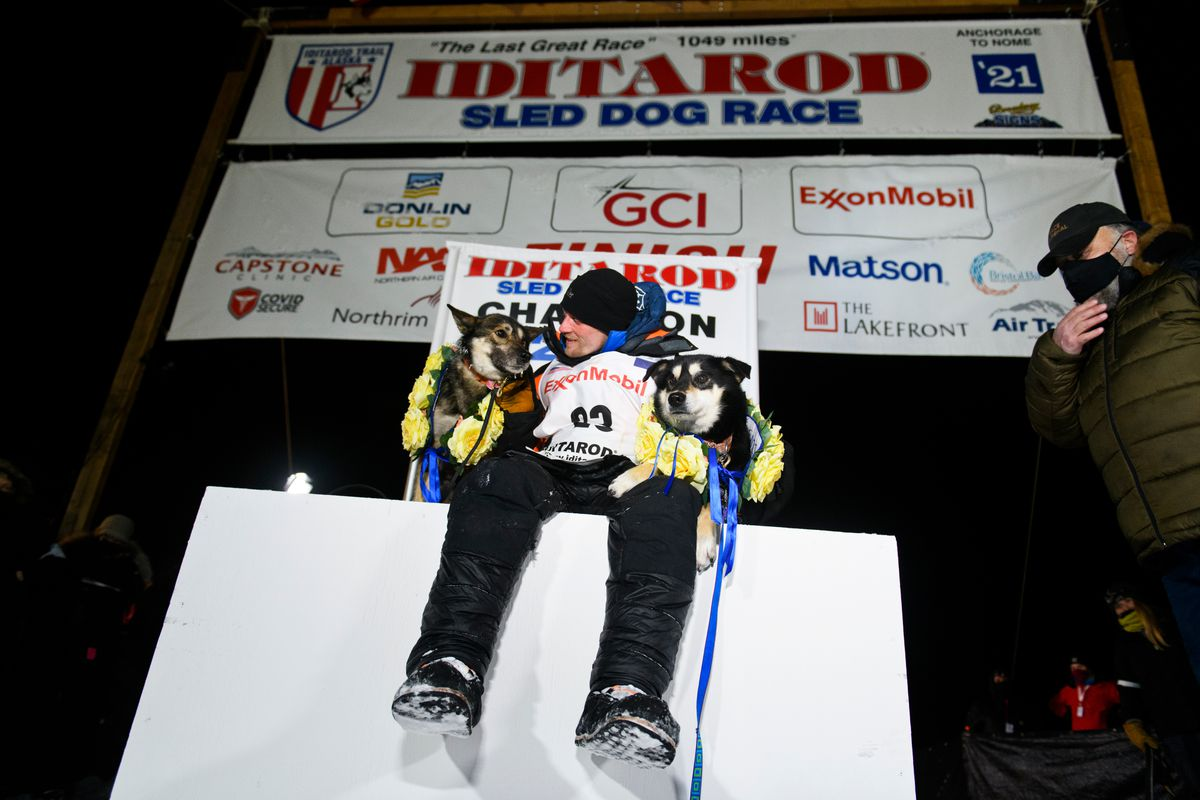 Dallas Seavey poses with his dogs North, left, and Gamble after winning the Iditarod Monday morning. (Marc Lester / ADN)