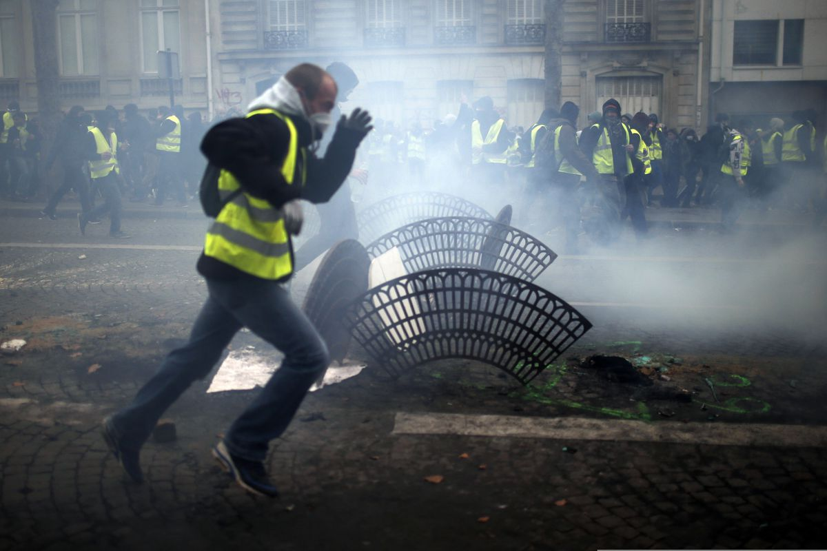 Demonstrators run away during clashes Saturday, Dec. 8, 2018 in Paris. Crowds of yellow-vested protesters angry at President Emmanuel Macron and France's high taxes tried to converge on the presidential palace Saturday, some scuffling with police firing tear gas, amid exceptional security measures aimed at preventing a repeat of last week's rioting. (AP Photo/Rafael Yaghobzadeh)