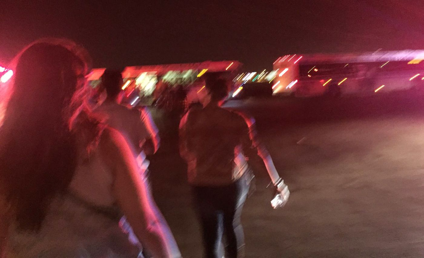 People who had been waiting at an airplane hangar after fleeing the Route 91 Harvest Festival make their way toward buses on the McCarran International Airport tarmac. They were transported to the Thomas and Mack Center, a sports arena, where they gave statements to police. (Photo by Erik Ross)