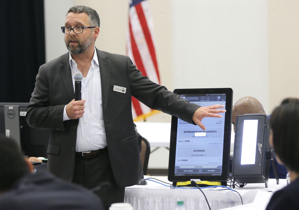 Eric Coomer from Dominion Voting in 2018 demonstrates his company's touch screen tablet that includes a paper audit trail at the second meeting of Secretary of State Brian Kemp's Secure, Accessible & Fair Elections Commission in Grovetown, Ga. Coomer, driven into hiding by death threats, has filed defamation lawsuits against President Donald Trump's campaign, two of its lawyers and some conservative media figures and outlets. (Bob Andres/Atlanta Journal-Constitution via AP, File)