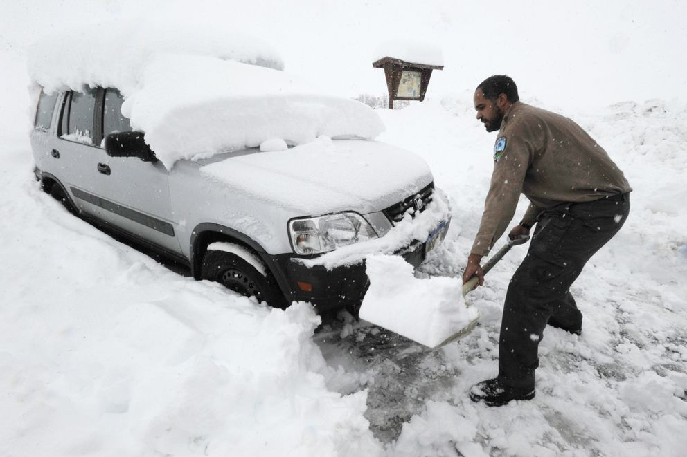 Park Specialist Hobbes Barber with the Alaska State Parks shovels snow at the parking lot between Hatcher Pass Lodge and Independence Mine on Wednesday, Oct. 9, 2019. This area has received more than twenty inches of snow in the past week. (Bill Roth / ADN)