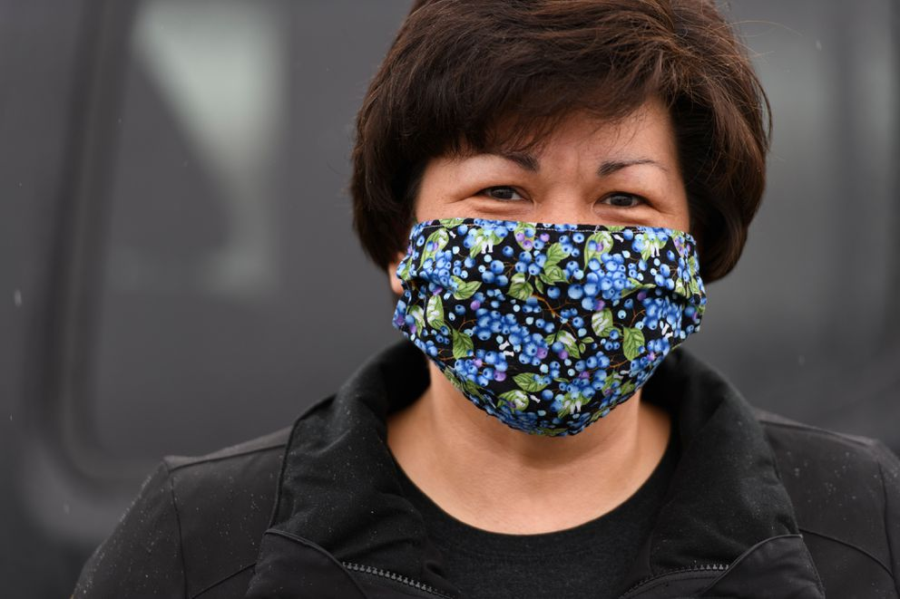 Dawn Samuelson shows one of her blueberry-print face coverings as drops off other masks she made for the Alaska Mask Makers effort on April 13, 2020. (Marc Lester / ADN)
