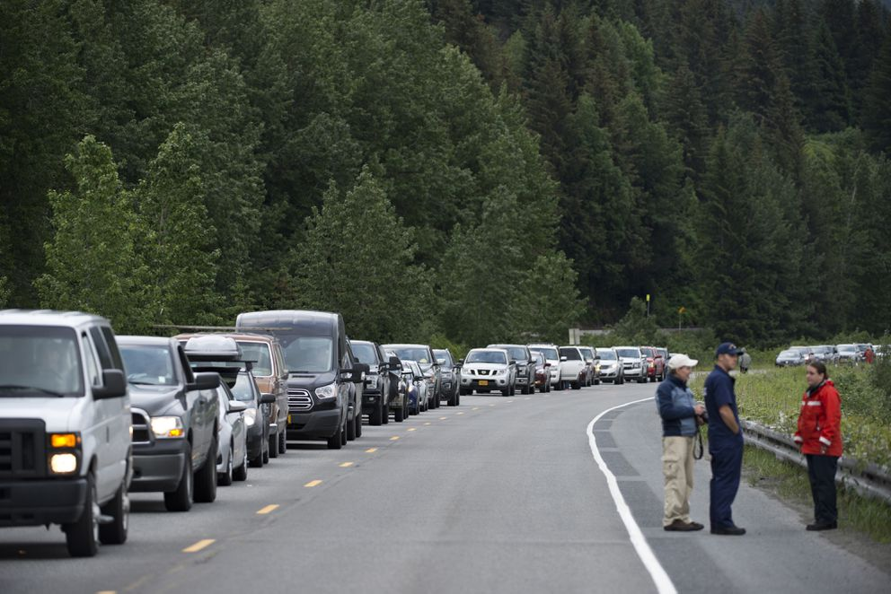Drivers wait outside their vehicles after an accident closed the Seward Highway south of Girdwood on June 30, 2017. (Marc Lester / Alaska Dispatch News)