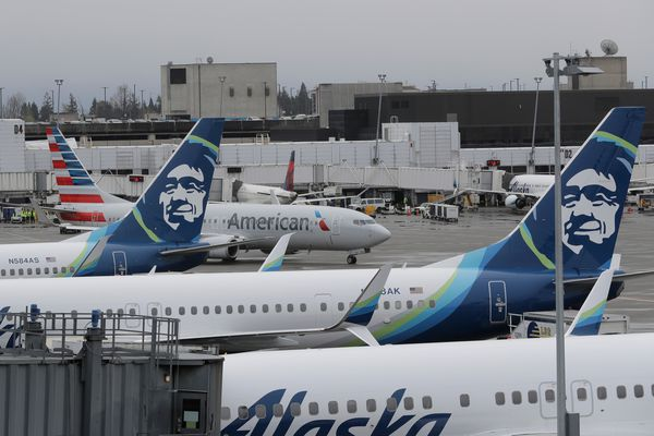 An American Airlines plane taxis past parked Alaska Airlines airplanes, Friday, April 13, 2018, at the Seattle-Tacoma International Airport in Seattle. (AP Photo/Ted S. Warren)