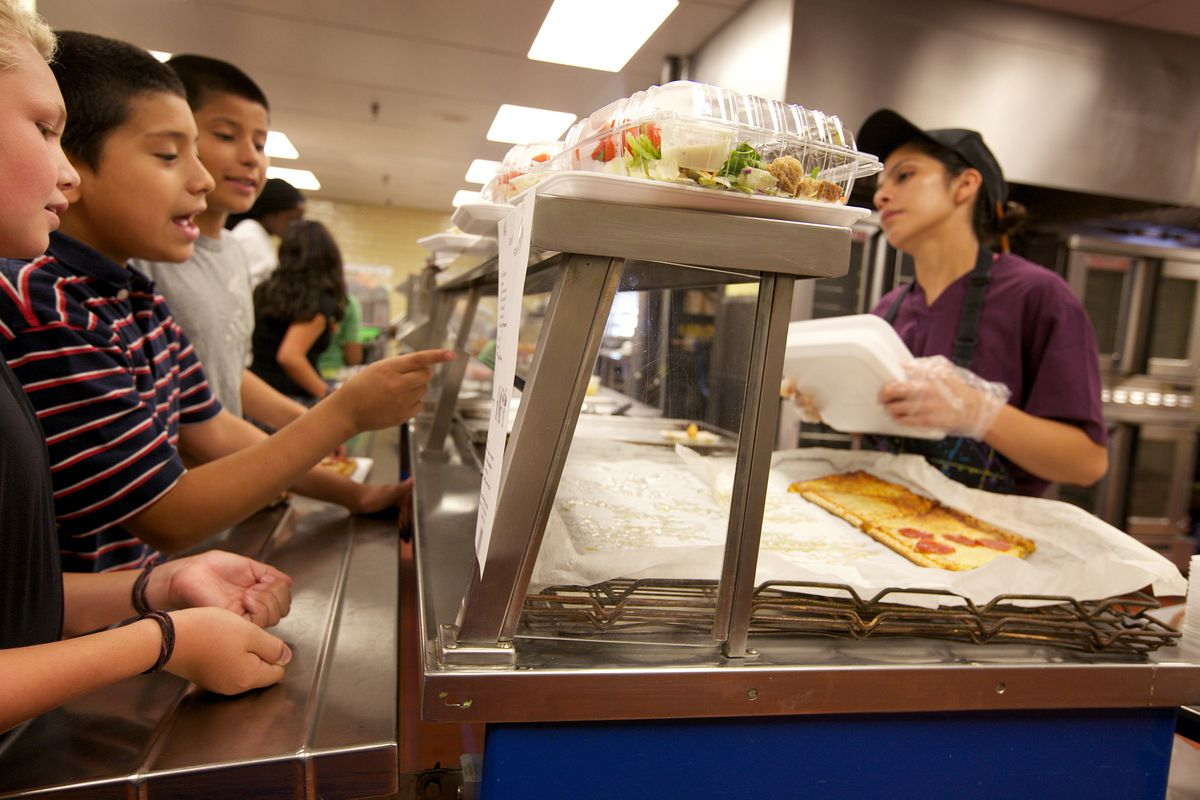 Cafeteria worker Imelda Pastora helps seventh- and eighth-graders as they make their way through a school lunch line in Montgomery County, Md. Taped to the counter is a sheet detailing the calories for the day's lunch, a new program in Montgomery County. (Photo for The Washington Post by Deb Lindsey)