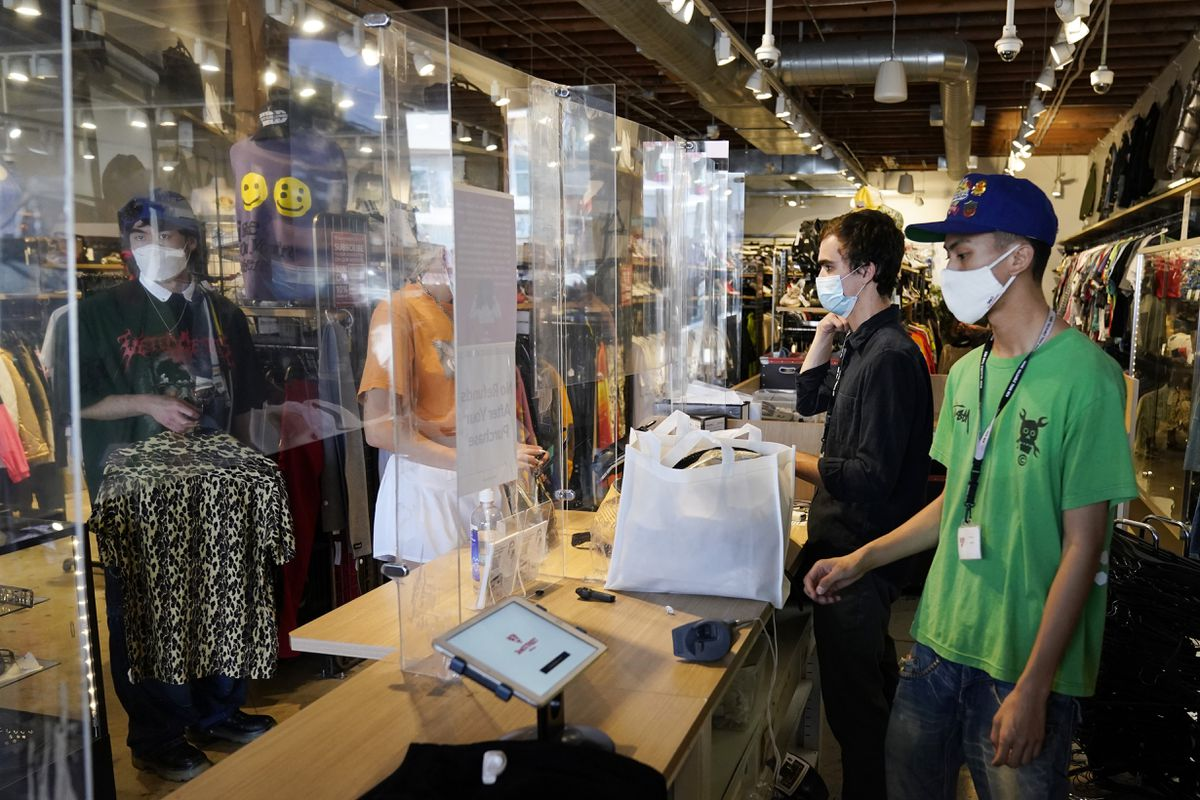 Employees check out customers at 2nd Street second hand store Monday, July 19, 2021, in the Fairfax district of Los Angeles. Los Angeles County has reinstated an indoor mask mandate due to rising COVID-19 cases. (AP Photo/Marcio Jose Sanchez)