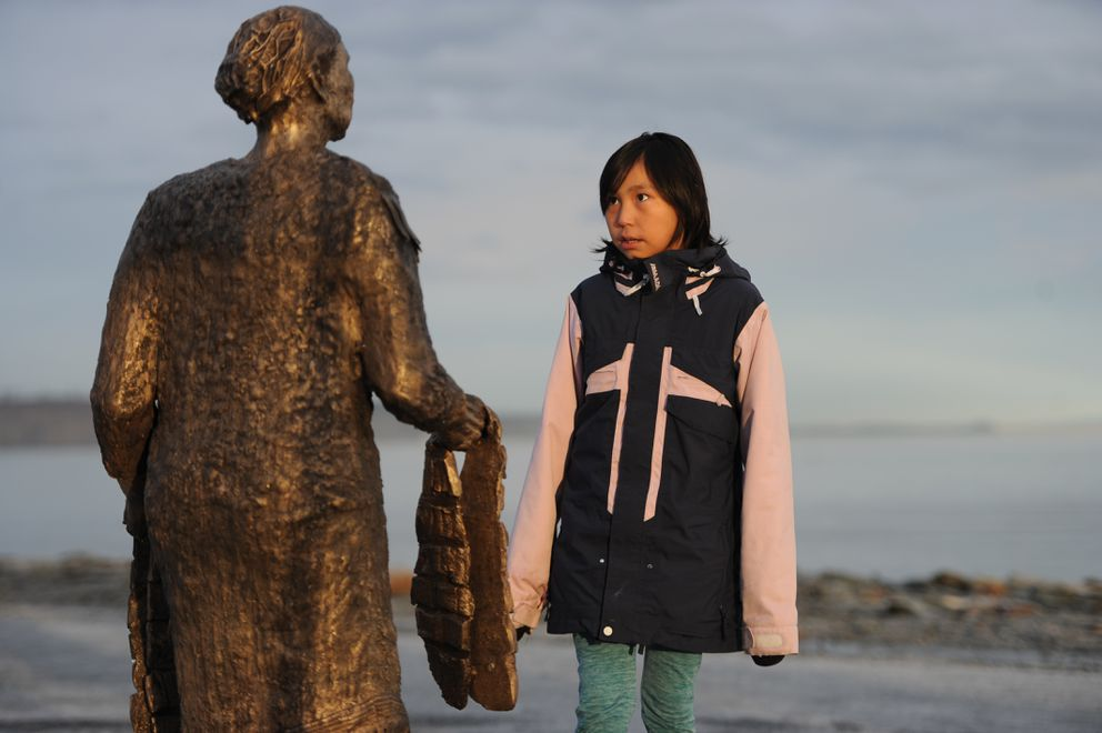 Ten-year-old Katya Daniels of Elim looks up at a bronze sculpture of Grandma Olga during a visit to the Ship Creek small boat launch near downtown Anchorage on Tuesday morning, Nov. 27, 2018. (Bill Roth / ADN)