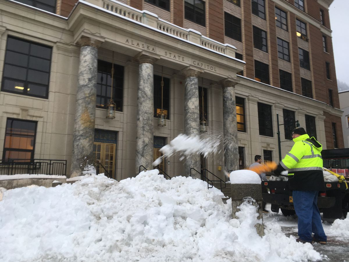 An Alaska Department of Administration employee shovels snow in front of the Alaska State Capitol on Monday, Jan. 21, 2019. Six inches of snow fell on Juneau on Sunday, and more fell early Monday morning. (James Brooks/ADN)