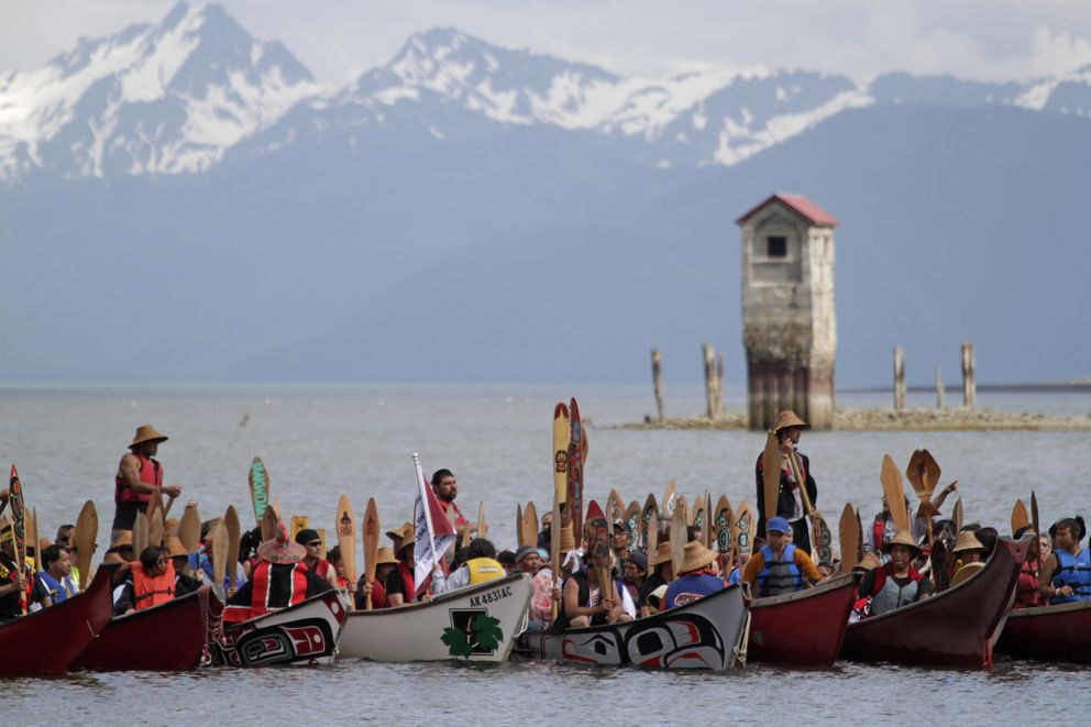 Alaska Native individuals paddle their canoes near the shore of Douglas Island's Sandy Beach on June 11, 2014 in Juneau for a ceremony observing the start of Celebration 2014. Celebration is a biennial event that brings together Alaska Natives from across Alaska for the state's largest cultural event. (AP Photo/James Brooks, Capital City Weekly)