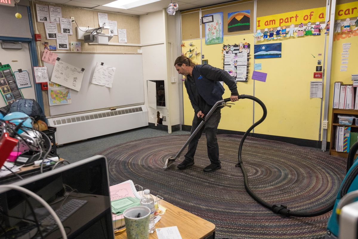 ABM employee Lucas Hopper uses a water extractor to vacuum water in Jennifer Harmon's 4/5th grade optional classroom at Susitna Elementary School. (Loren Holmes / ADN)