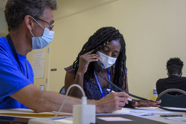 Michael Spatz, left, a volunteer with the Alexandria Medical Reserve Corps, helps AshaLetia Henderson through her first positive-case call as a coronavirus contact tracer in Alexandria, Va., in late June. (Washington Post photo by Jahi Chikwendiu)