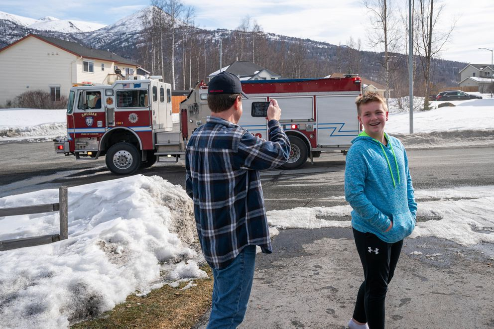 JJ Morton smiles as ambulances and fire engines from the Chugiak Volunteer Fire and Rescue Company drive by his house. (Loren Holmes / ADN)