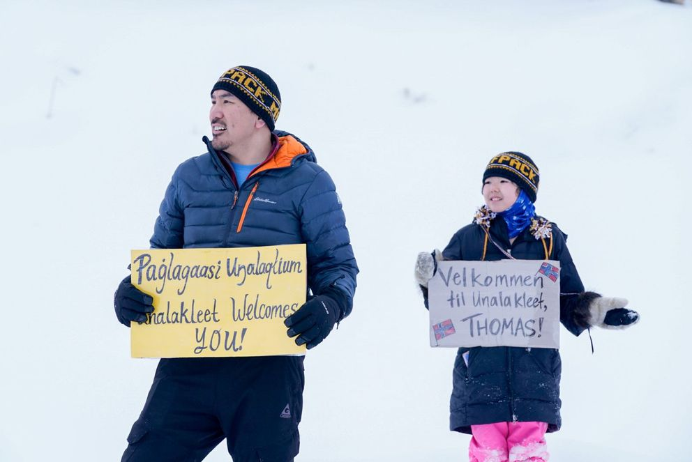 Marty Towarak and his daughter Aliana, 11, hold signs welcoming Thomas Waerner to Unalakleet on Sunday, March 15, 2020. Marty's sign is in Inupiaq, and Aliana's is in Norwegian. Aliana's mom is Norwegian. (Loren Holmes / ADN)