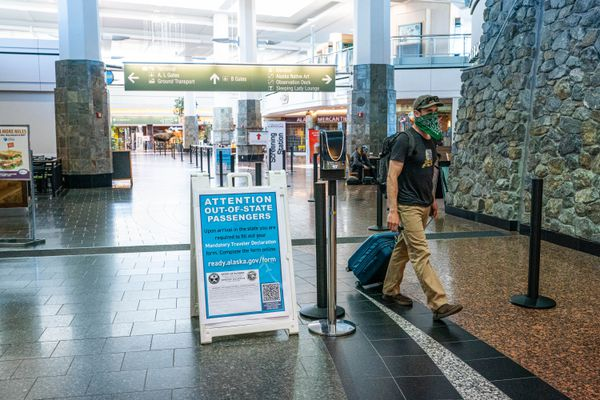 A person walks past a sign that gives out-of-state travelers instructions to fill out a declaration form online on Friday, June 5, 2020 at the Ted Stevens Anchorage International Airport. (Loren Holmes / ADN)