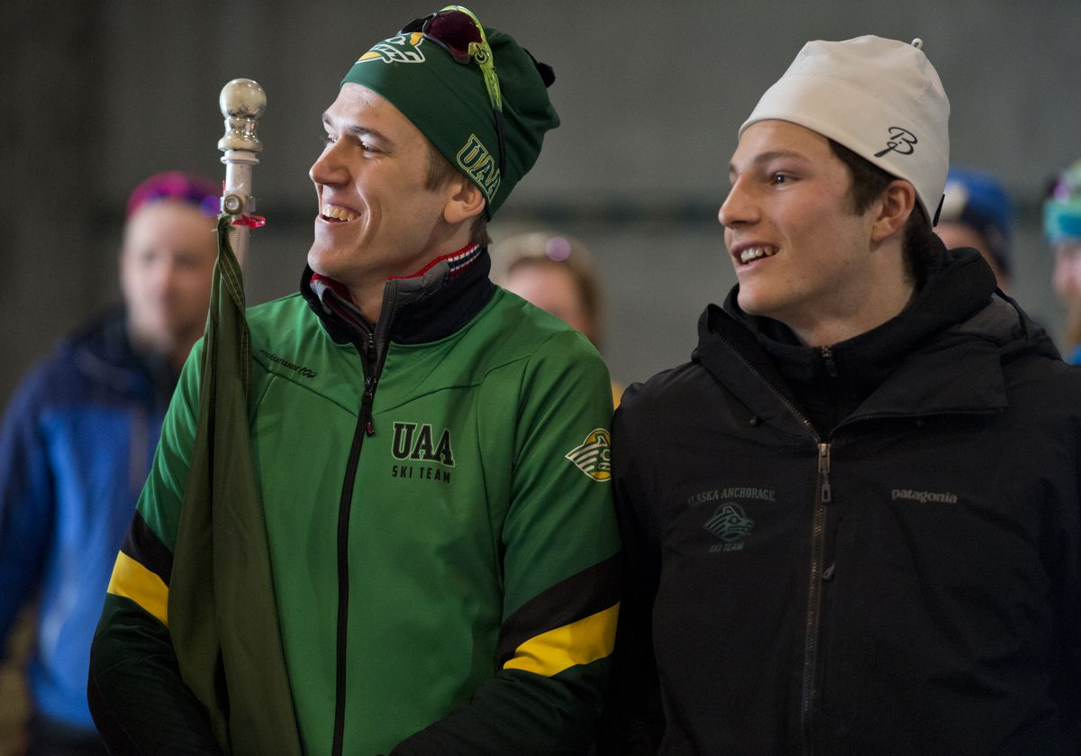 Sigurd Roenning, left, holds the Seawolves flag and stands with teammate JC Schoonmaker before the two took their places on the podium Monday at the UAA Invitational at Kincaid Park. (Marc Lester / ADN)
