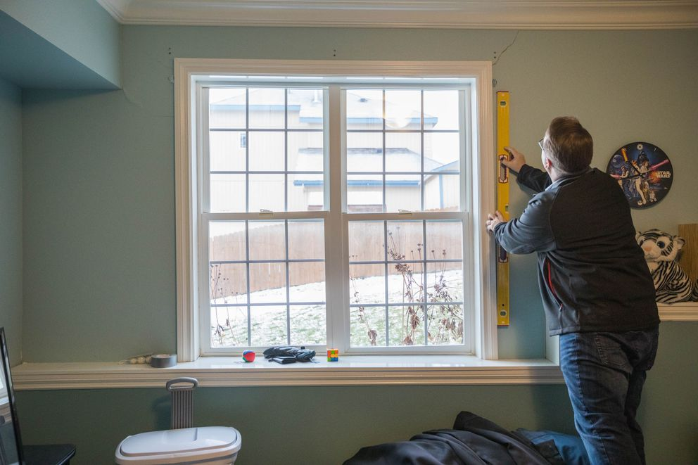 Eagle River homeowner Duncan Whitney holds a level to an out-of-plumb window in his home on Tuesday. (Loren Holmes / ADN)
