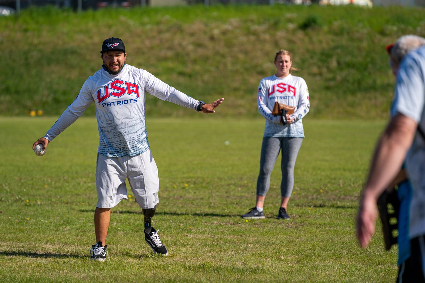 Saul Monroy, left, and Jessica Bosquez throw the ball to Special Olympics Alaska athletes at an event at Clark Middle School on Friday, June 11, 2021 in Anchorage. Monroy is a member of the USA Patriots softball team, and Bosquez is the team physical therapist. (Loren Holmes / ADN)