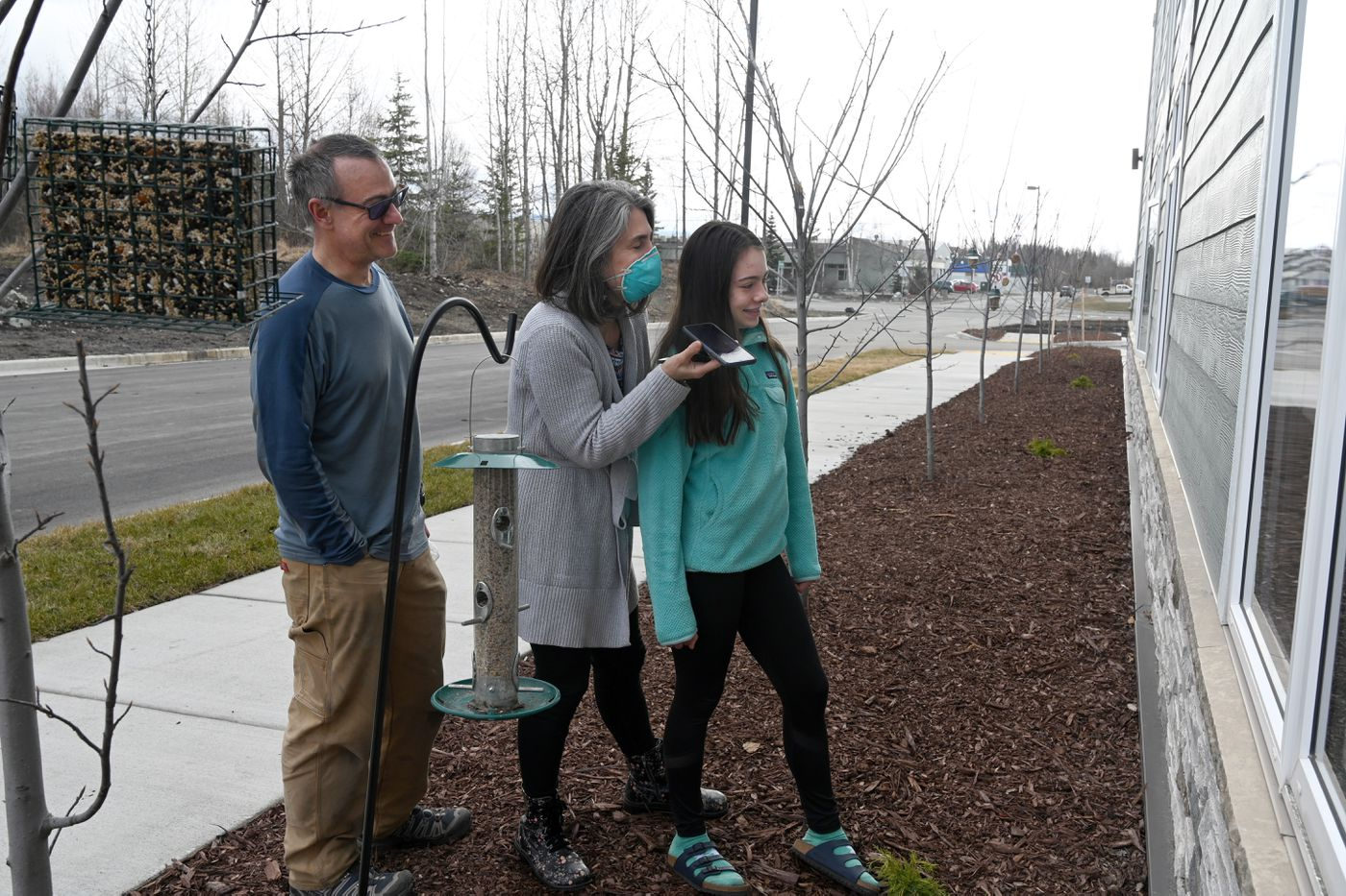 Robb Reeg, Michelle Hensel and their daughter 14-year-old Kaia talk to Michelle's father, Richard Hensel, through the window at Aspen Creek Senior Living, Wednesday, April 22, 2020. (Anne Raup / ADN)