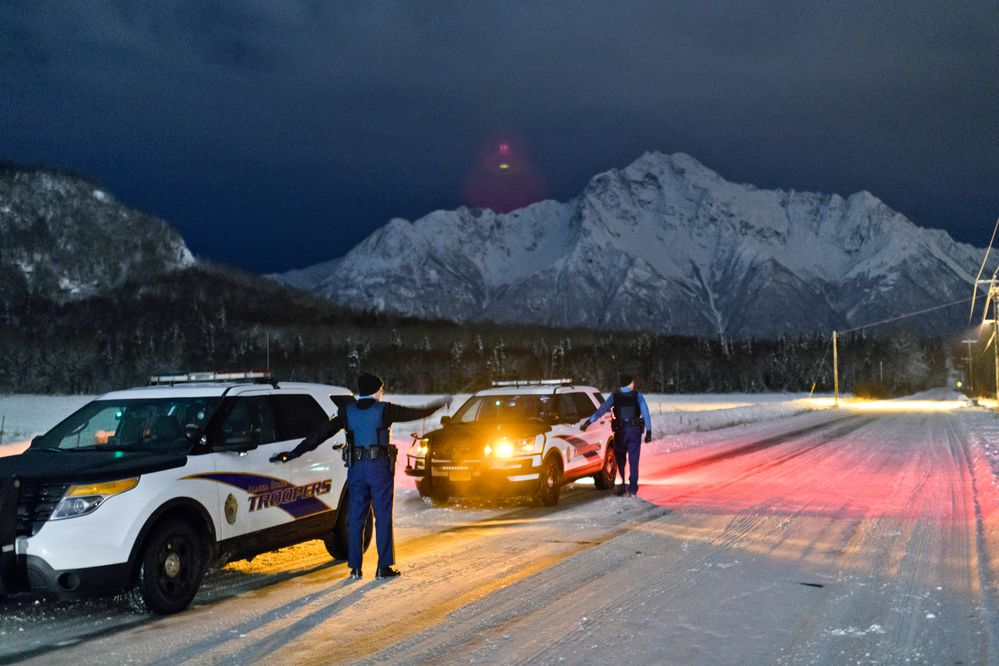 Alaska State Troopers Quinn Nardini, left, and Ryan Anderson talk on Bodenburg Loop, a street in Butte, Alaska, while looking for a man who had reportedly created a disturbance at a nearby store on November 18, 2019. (Marc Lester / ADN)