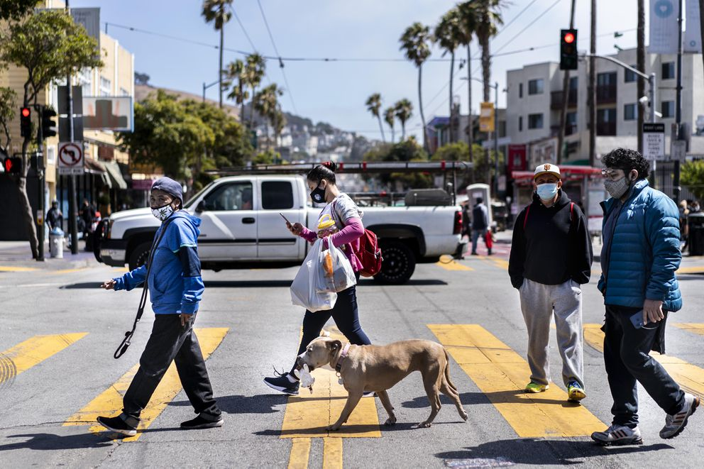 People and a pooch walk on Mission Street in San Francisco on July 13, 2020. Washington Post photo by Melina Mara